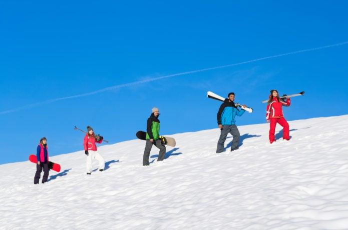 スノーボードとスキーをしている人々