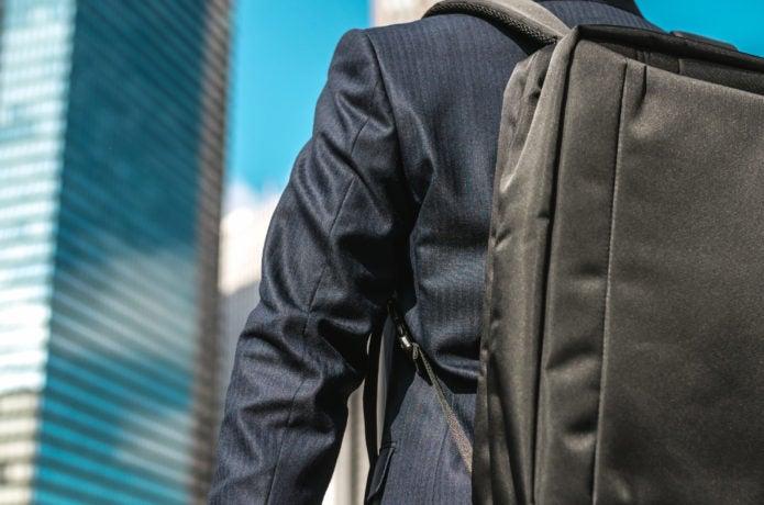 ビジネス用バックパックを背負っている男性