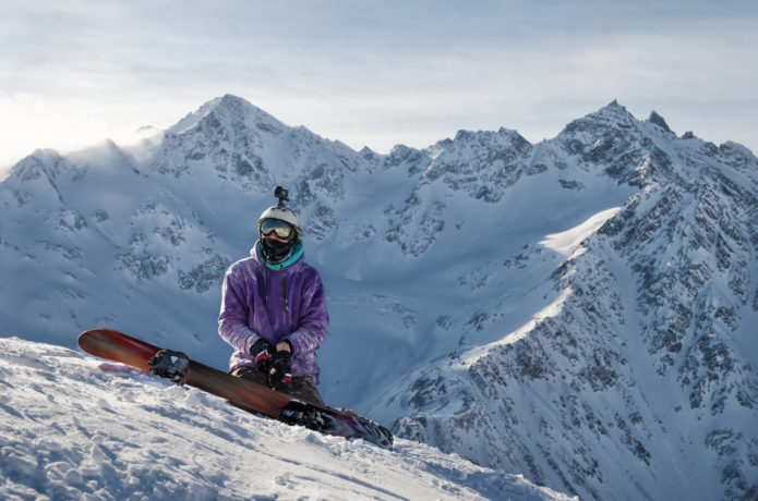 雪山でスノボをする男性